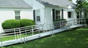 Aluminum ramp next to a white, panel house